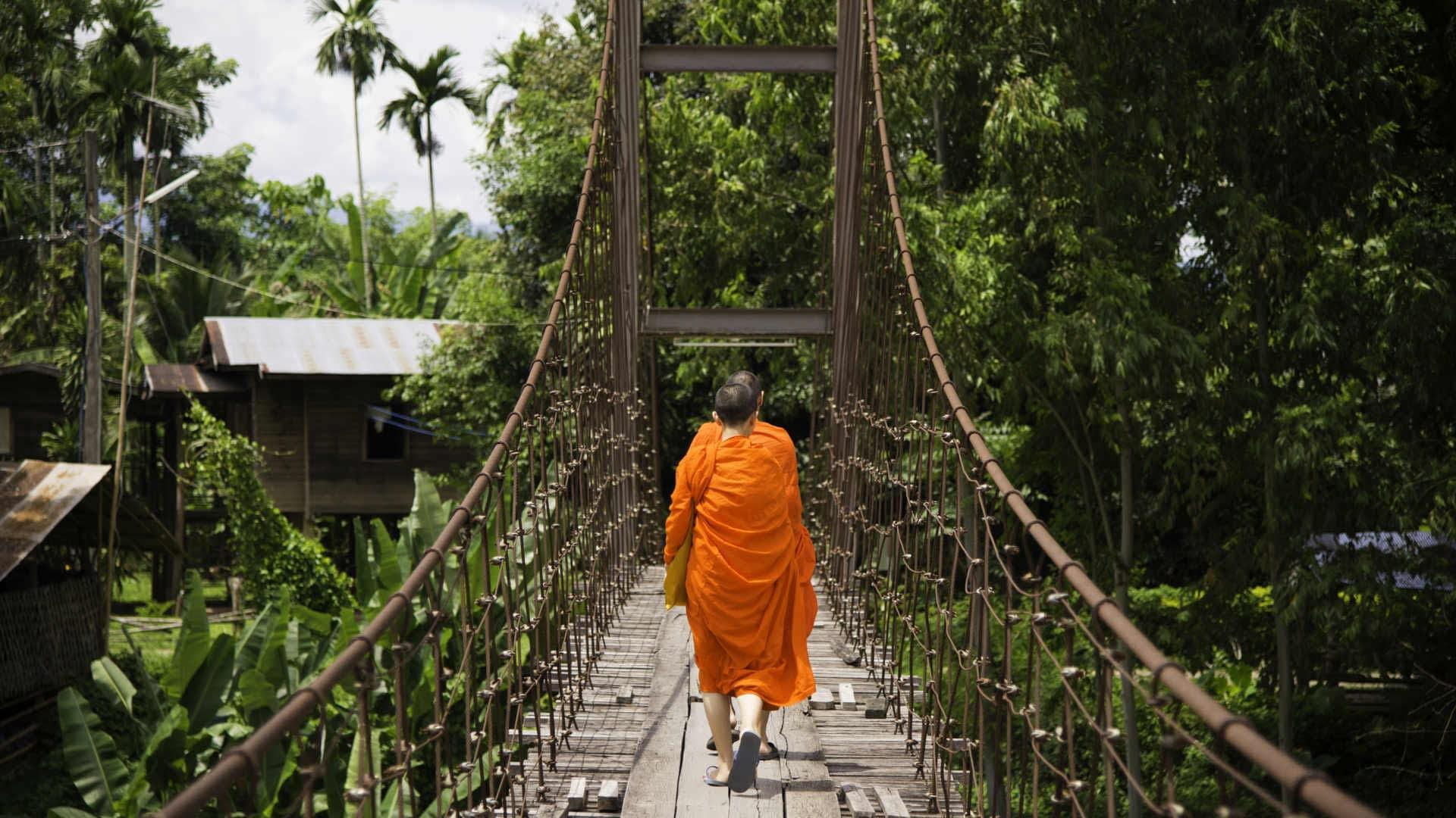 Buddhistische Mönche auf Hängebrücke Indochina