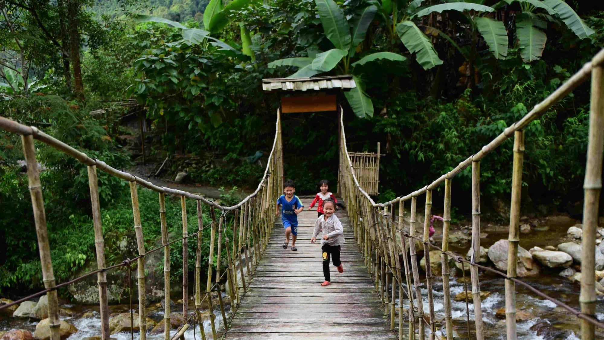 Go Indochine Kinder spielen auf Hängebrücke Vietnam