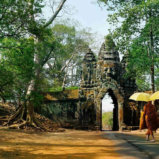 Monks with umbrella walking in Angkor Wat, Cambodia